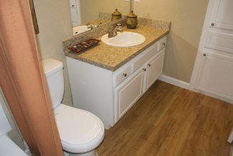 Very attractively remodled bathroom cabinet and sink featuring granite-style laminate countertop and back splash on a refaced cabinet repainted with a high gloss white enamel finish.