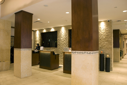 Hotel registration desks feature custom fine-wood construction with inlaid tile accent facing and granite counter and desktops.