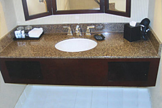 Custom walnut stained guest room vanities with granite countertop, and specially crafted picture framed mirrors.